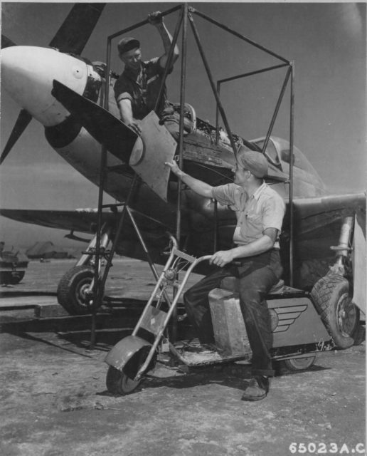 Total field mod. When your job is servicing the P-51s stationed on Iwo Jima, a motor scooter built from fuselage panels and cowling comes in handy. Notice the logo of North American Aviation on the scooter's side. (NARA)