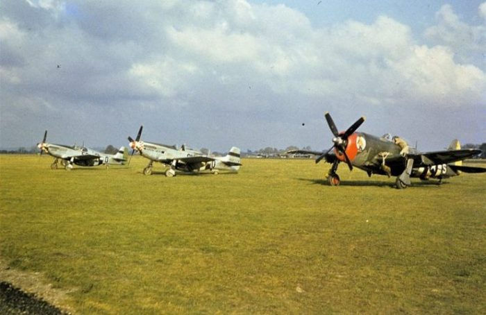 """A ground crewman works on a P-47 Thunderbolt beside P-51 Mustangs, (5Q-O, serial number 42-106886) nicknamed """"Swede"""" and (6N-O, serial number 44-14776) nicknamed """"Arrow Head"""", of the 339th Fighter Group at Mount Farm."""