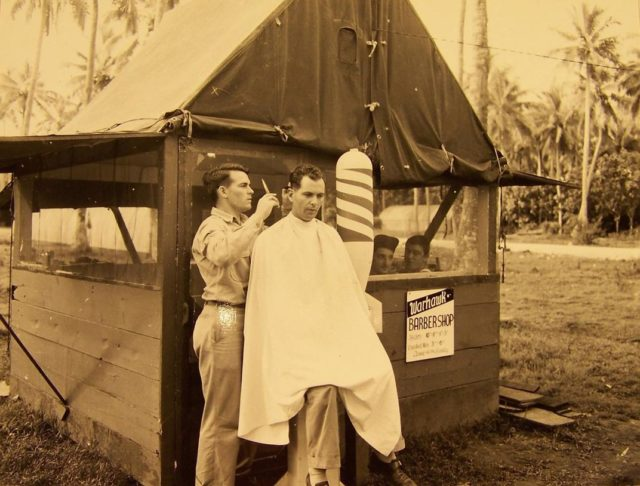 Looking for a trim on a South Pacific island? Look for the Warhawk Barber Shop with its barber pole made of a bomb shell. (NARA)