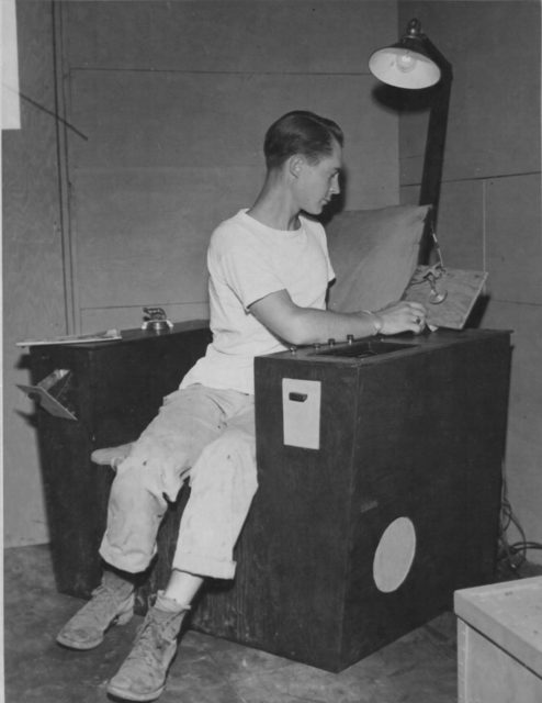 Sergeant Ray Petit of the 15th Air Force in Italy built a chair using the wood crate from a belly tank. His chair is equipped with a reading light, ashtray, magazine rack, and a radio that turns off on a timer once he dozes off. (NARA)