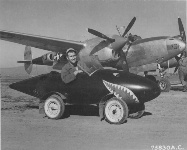 United States Army Air Forces Lockheed P-38L Lightning aircraft ( Serial Number – 44-25734 ) and a ground crew member of the 94th Fighter Squadron 1st Fighter Group, poses in his self-styled auto made from salvaged Lockheed P-38 Lightning parts including a fuel tank with wheels added and a plexiglass windshield. This P-38 while assigned to 1st FG, 71st FS was shot down by AAA near Munich April 15, 1945.