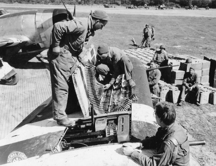 9th Air Force mechanics refill the compartments for the 4 12.7 machine guns on the left side of a Republic P-47 Thunderbolt.