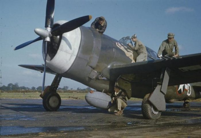 The ground crew servicing the Republic P-47 Thunderbolt flown by Captain Johnson. Sergeant George Baltimore is working on the petrol tank, Corporal Jack Kazanjac on top of the engine, Sergeant Howard Buckner by the cockpit, and Private Albert Asplint on the wing.