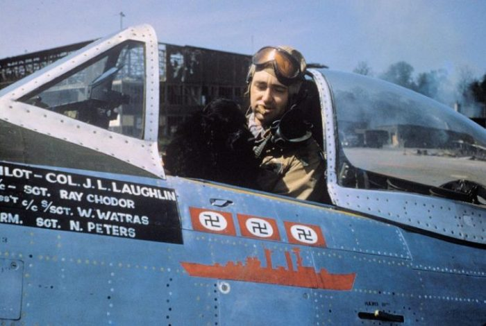 """Colonel J.L. Laughlin, of the 362nd Fighter Group, smokes a cigar with his dog mascot """"Prince"""" inside the cockpit of his P-47D serial 44-33287 """"Five By Five"""" (coded B8-A)"""