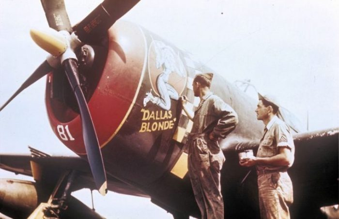 """Two ground crew add the finishing touches to the nose art of a 352nd Fighter Group P-47 Thunderbolt nicknamed """"Dallas Blonde"""". Handwritten on slide casing: 'P-47, 352nd F.G.'"""