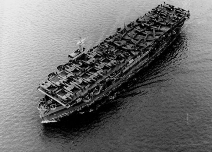The U.S. Navy escort carrier USS Barnes (ACV-20) underway in the Pacific Ocean on 1 July 1943, transporting U.S. Army Air Forces Lockheed P-38 Lightning and Republic P-47 Thunderbolt aircraft.