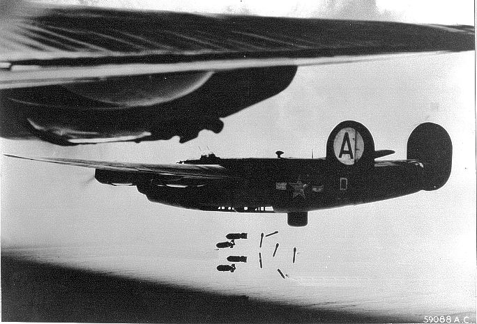 A B-24 dropping its bomb load. Note the lack of bomb bay doors externally on the aircraft, and the deployed belly turret.