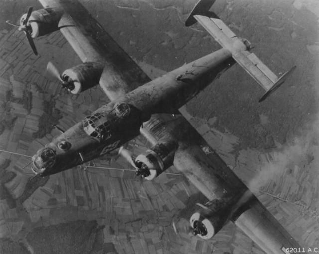 "A damaged B-24 Liberator ""Burma Bound"", of the 451st Bomber Group returns to base after a raid on Munich."