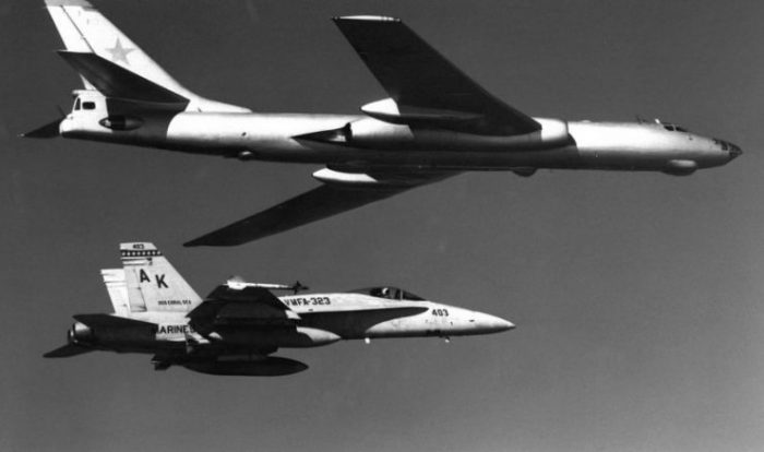 A Soviet Tupolev Tu-16 Badger aircraft being escorted by a U.S. Marine Corps McDonnell Douglas F/A-18A Hornet aircraft from Marine fighter-bomber squadron VFMA-323 Death Rattlers in 1985.