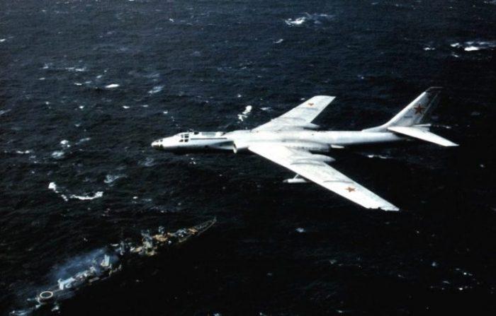 "A Soviet Tupolev Tu-16 (NATO reporting code ""Badger"") in flight in 1984 above a Nikolaev class cruiser (NATO reporting code ""Kara"")."