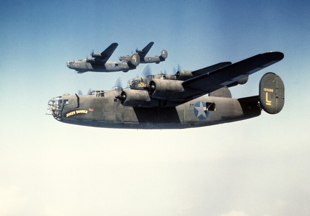 An air-to-air left side view of four B-24 Liberator aircraft in formation. The B-24 was built for World War II combat.