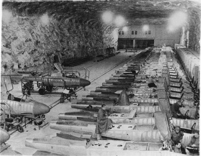 An underground production line of He 162 aircraft. When viewing these conditions, its easy to understand why the workmanship declined so dramatically in the later years of the war. Image by Bundesarchiv CC BY-SA 3.0 de.