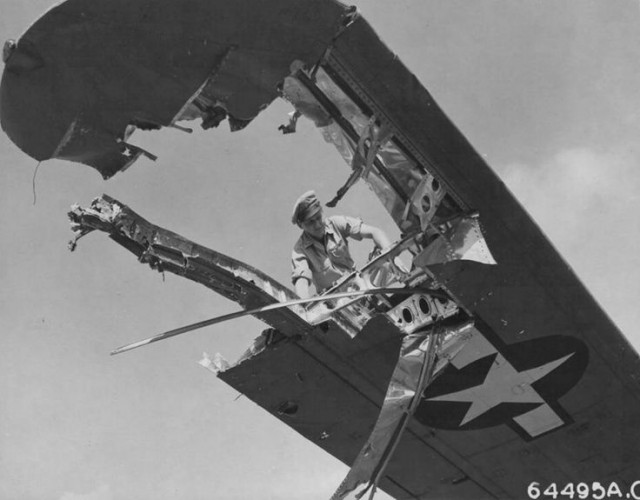 """Crew member examines wing of a Consolidated B-24 """"Liberator"""" which was badly-damaged during pre-invasion raid over Iwo Jima. Marianas Islands"""