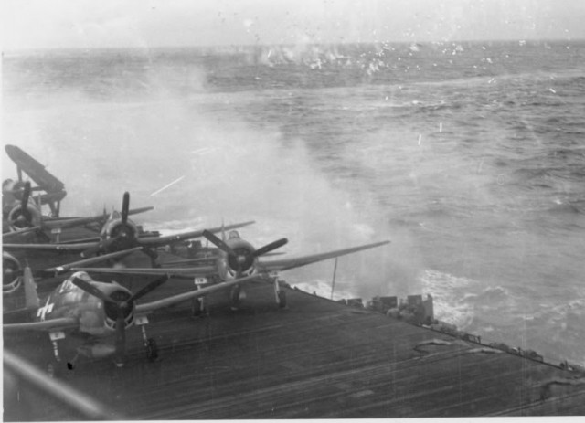 Grumman F6F-5 Hellcats of fighter squadron VF-19 Bulldogs and a Curtiss SB2C Helldiver of bombing squadron VB-19 on the deck of the aircraft carrier USS Lexington (CV-16) during an attack in November 1944.