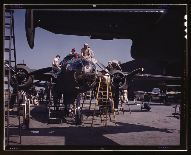 "Employees on the ""Sunshine"" assembly line at North American's plant put the finishing touches on another B-25 bomber, Inglewood, California. In addition to the battle-tested B-25 (""Billy Mitchell"") bomber, used in General Doolittle's raid on Tokyo, this plant produces the P-51 (""Mustang"") fighter plane which was first brought into prominence during the British raid on Dieppe"