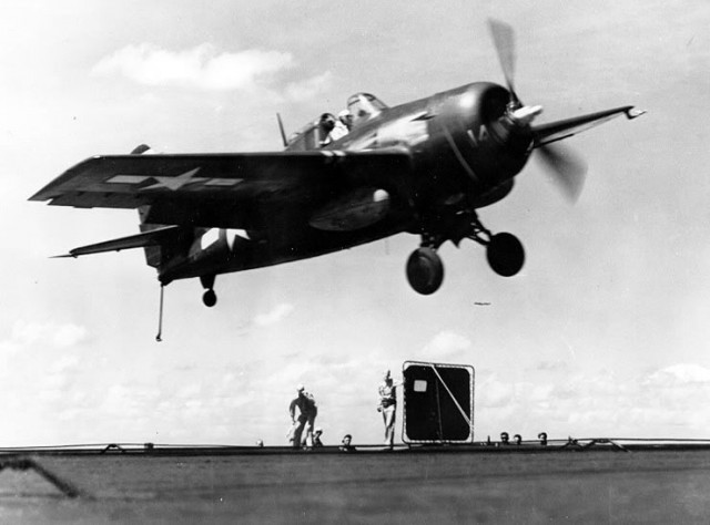 """A U.S. Navy Grumman FM-2 Wildcat fighter gets a """"wave-off"""" from the Landing Signal Officer while attempting to land on the escort carrier USS Makin Island (CVE-93), about 1944/45."""