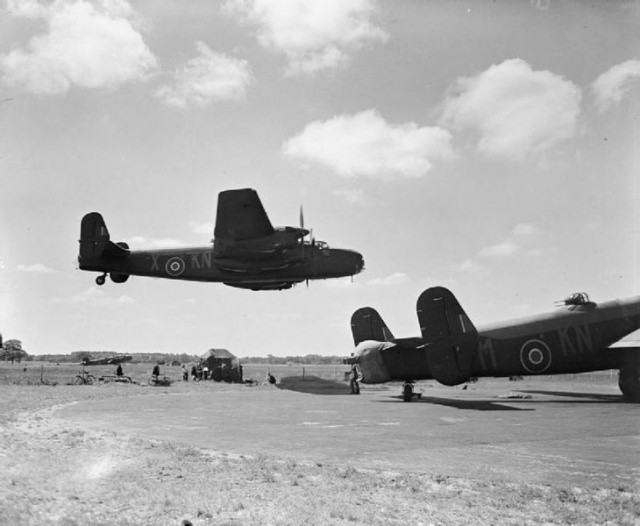 Halifax B Mark II Series 1 (Special), JB911 KN-X, of No. 77 Squadron RAF, making a low level pass over other aircraft of the squadron at Elvington, Yorkshire.