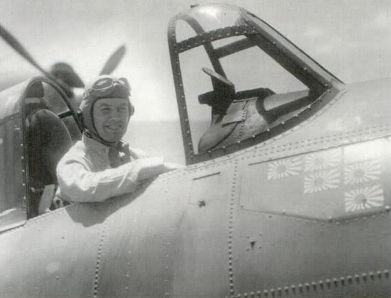 Jimmy Flatley sits in his F4F-4 Wildcat—decorated with his victories at Coral Sea, Santa Cruz, Guadalcanal, and Rennell Island—aboard the USS Enterprise's deck. 1943
