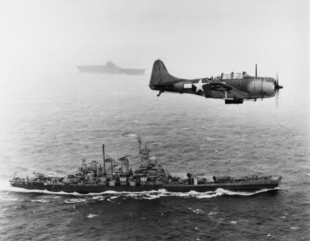 A U.S. Navy Douglas SBD-5 Dauntless of bombing squadron VB-16 flies an antisubmarine patrol low over the battleship USS Washington (BB-56) en route to the invasion of the Gilbert Islands, 12 November 1943. The ship in the background is USS Lexington (CV-16), the aircraft's home carrier.