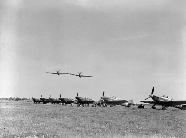 Two Royal Air Force Hawker Hurricane Mark IIs of No. 43 Squadron RAF make a low level pass over other aircraft of the Squadron, lined up at Tangmere, Sussex (UK)