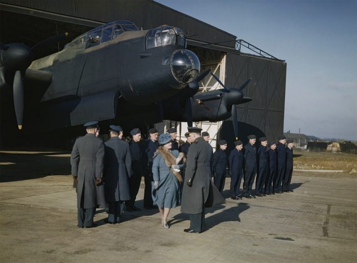 HM Queen Elizabeth inspecting flight and ground crews on a visit to Warboys, a station of No 8 Pathfinder Group. An Avro Lancaster of No 156 Squadron, Royal Air Force is seen in a T2 hangar. 10 February 1944