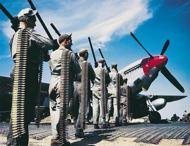 American ground crew preparing to arm P-51 Mustang fighter at an airfield with six M2 machine guns and 0.50 caliber ammunition, date unknown