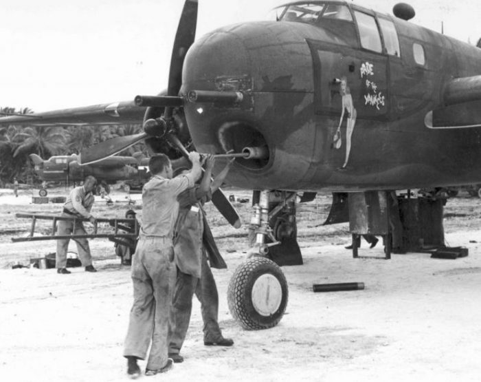 Armorer cleaning the bore of a 75mm cannon mounted in a B-25G Mitchell bomber of the 820th Bomb Squadron, Tarawa, Gilbert Islands; March-April 1944.