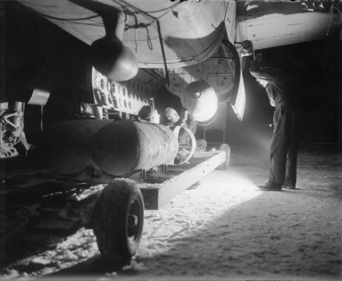 Armorers load four 1,000-lb MC bombs into the bomb-bay of a North American B-25 Mitchell, for an early morning sortie from B58 Melsbroek, Belgium.