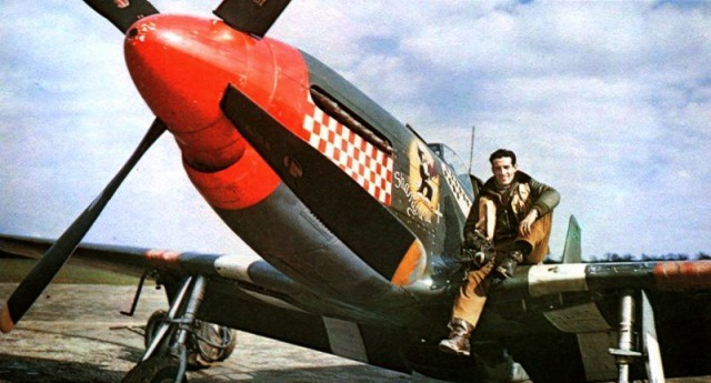 """USAAF Capt Don Gentile sits on the wing of his P-51B Mustang """"Shangri-La"""" of the 336th Fighter Squadron at RAF Debden, Essex, England, UK; 1944-45."""