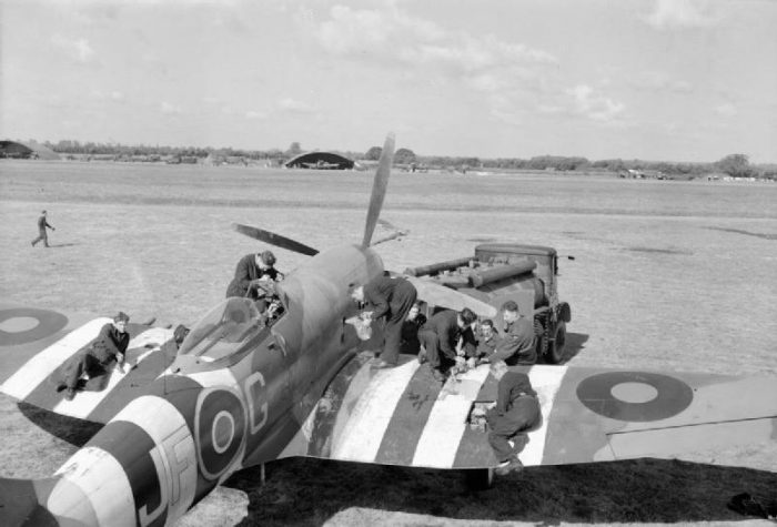 Ground crew refuel and rearm a Hawker Tempest. The stripes on top of the wings and fuselage signify this image was most likely taken in June 1944.
